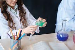 Los alumnos expertos que participan en la química experimentan en la escuela Foto de archivo libre de regalías