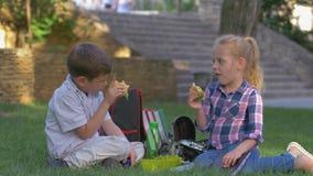 Los alumnos hambrientos comen los bocadillos durante el tiempo del almuerzo que se sienta en césped en patio almacen de metraje de vídeo