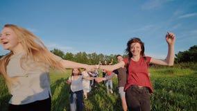 Los alumnos mayores felices huyen y lanzan de sus carteras contra la puesta del sol Días escolares felices de la conclusión Cámar almacen de metraje de vídeo