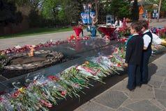 Los alumnos pusieron las flores al fuego eterno en el monumento Imagen de archivo