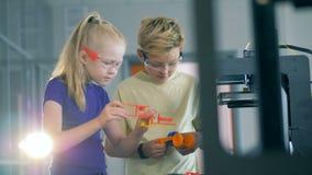 Los alumnos trabajan con una impresora, llevando a cabo modelos del plástico 3D almacen de video
