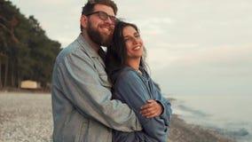 Los amantes abrazan cerca del mar, los pares disfrutan de la opinión hermosa del mar por la tarde almacen de metraje de vídeo