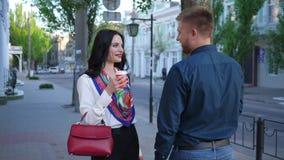 Los amantes con café en manos van a encontrarse en la calle de la ciudad almacen de video