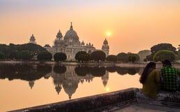 Los amantes disfrutan de una puesta del sol serena romántica en Victoria Memorial Kolkata, la India Imágenes de archivo libres de regalías