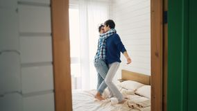 Los amantes jovenes alegres están bailando en la cama en casa que se divierte en dormitorio y que ríe negligentemente Juventud fe almacen de video