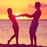 Los amantes juntan tener romance de la diversión en la playa de la puesta del sol Imagenes de archivo