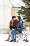 Amantes que se besan en el banco Imagen de archivo