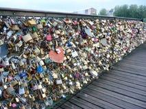 Los amantes se escudan en la verja del puente de Pont des Arts en París Foto de archivo