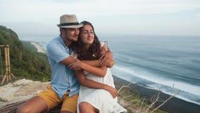 Los amantes se sientan en el lugar romántico, abrazo, hermosa vista en el fondo, cámara lenta almacen de metraje de vídeo