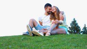 Los amantes se sientan en la hierba y el abrazo almacen de metraje de vídeo
