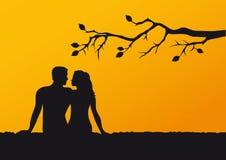 Los amantes siluetean en la puesta del sol Foto de archivo libre de regalías