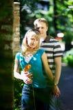 Los amantes sirven y mujer en fecha romántica en parque Fotos de archivo