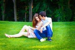 Los amantes sirven y mujer que se sienta en la hierba Fotos de archivo libres de regalías