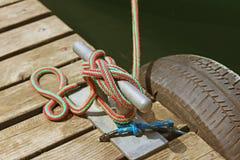 Los amarres se construyen para un pato en un embarcadero de madera Reutilización del neumático de automóvil para la depreciación  Imagenes de archivo