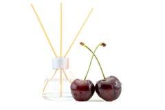 Los ambientadores de aire con la cereza sospechan en un tarro de cristal hermoso con los palillos aislados en un blanco Imagen de archivo libre de regalías