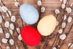 Los amentos y los huevos de Pascua envolvieron la secuencia de lana en el tablero rústico, decoración festiva Fotografía de archivo