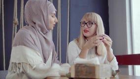 Los amigos étnicos multi adultos de las mujeres están cotilleando en café en día de invierno almacen de metraje de vídeo
