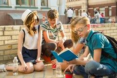 Los 4 amigos adolescentes felices o los estudiantes de la High School secundaria se están divirtiendo, hablando, leyendo el teléf Imagen de archivo