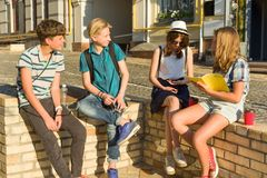 Los 4 amigos adolescentes felices o los estudiantes de la High School secundaria se est?n divirtiendo, hablando, leyendo el tel?f imagen de archivo libre de regalías
