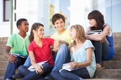 Los amigos adolescentes que se sientan en universidad caminan afuera Imagen de archivo