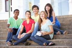 Los amigos adolescentes que se sientan en universidad caminan afuera Imagen de archivo libre de regalías