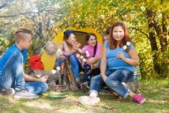Los amigos adolescentes se sientan en sitio para acampar con la melcocha Fotos de archivo