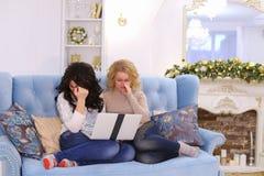 Los amigos agradables divertidos pasan la tarde agradable en el ordenador, sentada o Fotografía de archivo