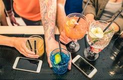 Los amigos agrupan el cóctel de consumición en el restaurante de la barra de la moda fotografía de archivo