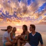 Los amigos agrupan en la playa de la puesta del sol que se divierte con la guitarra Fotografía de archivo