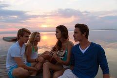 Los amigos agrupan en la playa de la puesta del sol que se divierte con la guitarra Foto de archivo libre de regalías