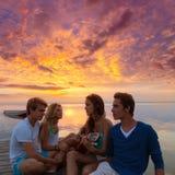 Los amigos agrupan en la playa de la puesta del sol que se divierte con la guitarra Foto de archivo
