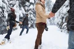 Los amigos agrupan la nieve Forest Young People Walking Outdoor de dos pares foto de archivo libre de regalías