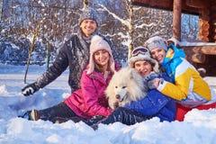 Los amigos alegres con el perro pasan vacaciones de invierno juntas en la cabaña de la montaña imagenes de archivo