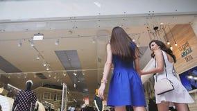Los amigos alegres entran en la parte trasera de la cámara lenta de la tienda de la moda almacen de video