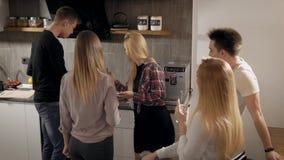 Los amigos alegres están probando la comida cocinada por su compinche en cocina durante partido, los cócteles de consumición y la almacen de metraje de vídeo