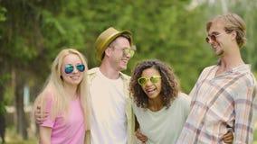 Los amigos alegres jovenes que bromean y que ríen, teniendo buen fin de semana en parque, se relajan almacen de metraje de vídeo