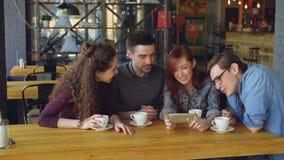 Los amigos apuestos están mirando el vídeo interesante y lo están discutiendo mientras que beben té en la tabla en café acogedor  almacen de video