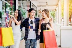Los amigos asiáticos que hacen compras son que caminan y que hacen compras en stre de las compras Imagen de archivo libre de regalías
