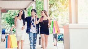 Los amigos asiáticos que hacen compras son que caminan y que hacen compras en stre de las compras Foto de archivo