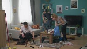 Los amigos ayudan limpio a la sala de estar después del partido metrajes