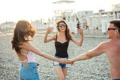 Los amigos bailan en la playa bajo luz del sol de la puesta del sol, divirtiéndose, feliz, gozan imagen de archivo libre de regalías