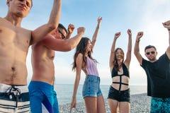 Los amigos bailan en la playa bajo luz del sol de la puesta del sol, divirtiéndose, feliz, gozan foto de archivo