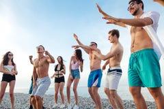 Los amigos bailan en la playa bajo luz del sol de la puesta del sol, divirtiéndose, feliz, gozan fotos de archivo
