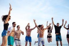 Los amigos bailan en la playa bajo luz del sol de la puesta del sol, divirtiéndose, feliz, gozan fotografía de archivo
