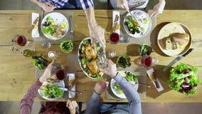 Los amigos caucásicos del cuadro cuatro de arriba de visión superior que comen el almuerzo, bebiendo, tuestan así como el pollo,  almacen de metraje de vídeo