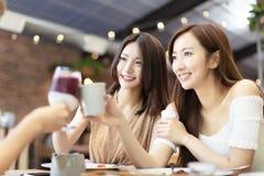 Los amigos celebran con la tostada y el tintineo en restaurante imagen de archivo