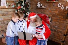 Los amigos cercanos de niños con Santa Claus utilizan el ordenador portátil en Cristo Imágenes de archivo libres de regalías