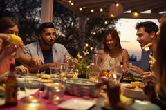 Los amigos comen y hablan en un partido de cena en un patio, cierre para arriba foto de archivo