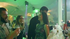 Los amigos comunican en partido, los cócteles de la bebida y tener un buen rato juntos en una barra almacen de metraje de vídeo