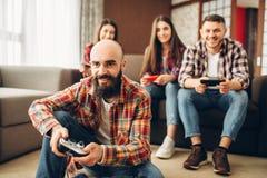 Los amigos con las palancas de mando juegan la consola de la TV en casa fotos de archivo libres de regalías